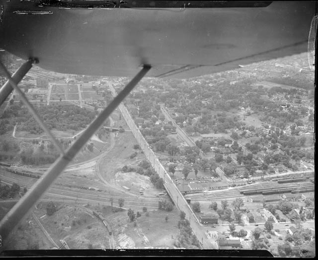 Williams Hill (left between wing struts) was really a hill in 1949 when a Saint Paul Pioneer Press Dispatch photographer took this picture. The Mississippi Street passenger car yard and shop of the Great Northern Railway are on the lower right. Courtesy MNHS