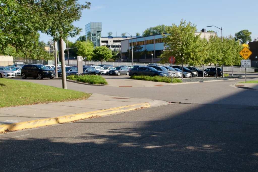 I saw buildings beyond the dead end sign so I rode over to inspect. The cars are parked in Lot L.