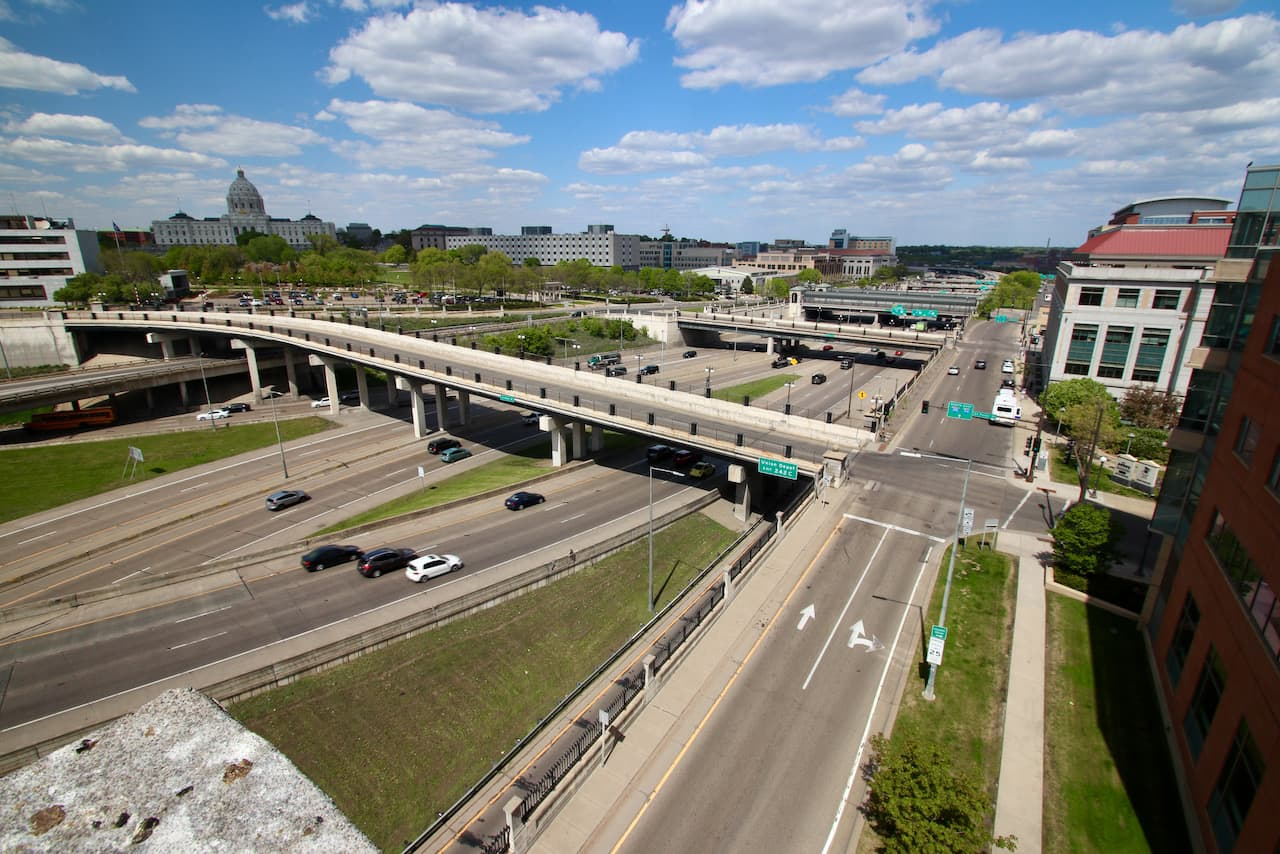Looking northeast and another section of I-94/35E and the St. Peter, Wabasha and Cedar Street bridges. The buildings, beginning with the Capitol, include the Centennial Office Building, the Ag Department/Health Department lab building, Department of Revenue and Regions Hospital.